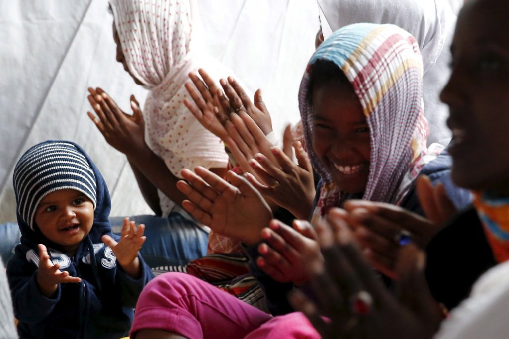 "A baby from Ethiopia sits in the middle of women from Ethiopia and Eritrea who pray and sing together during Sunday mass at the makeshift church in ""The New Jungle"" near Calais"